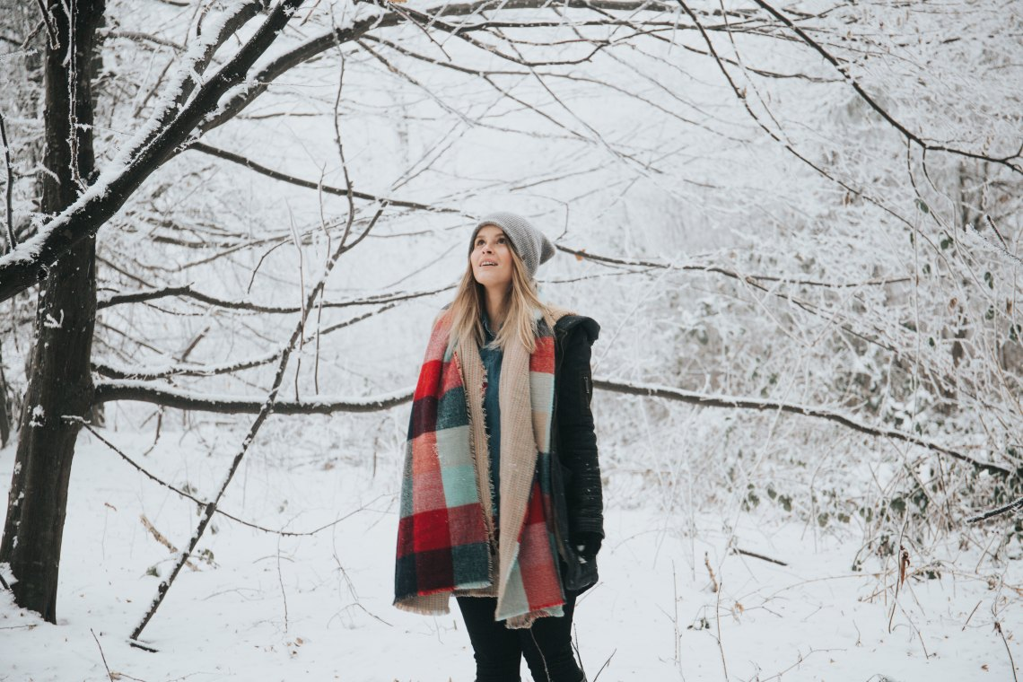 girl looking up at a tree in the snow