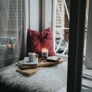 candle, hot chocolate on window seat