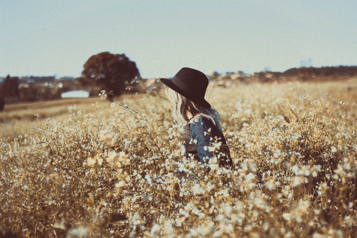 a girl in a hat in a field of flowers