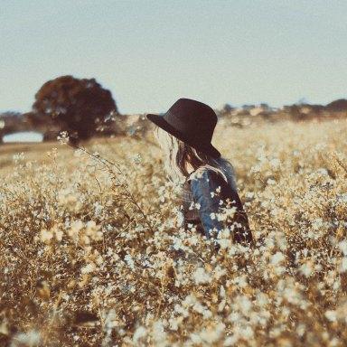 a girl in a hat in a field of flowers
