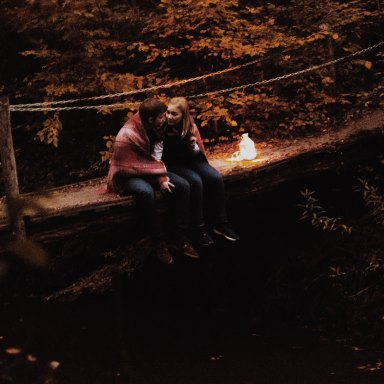 couple sitting together on a bridge