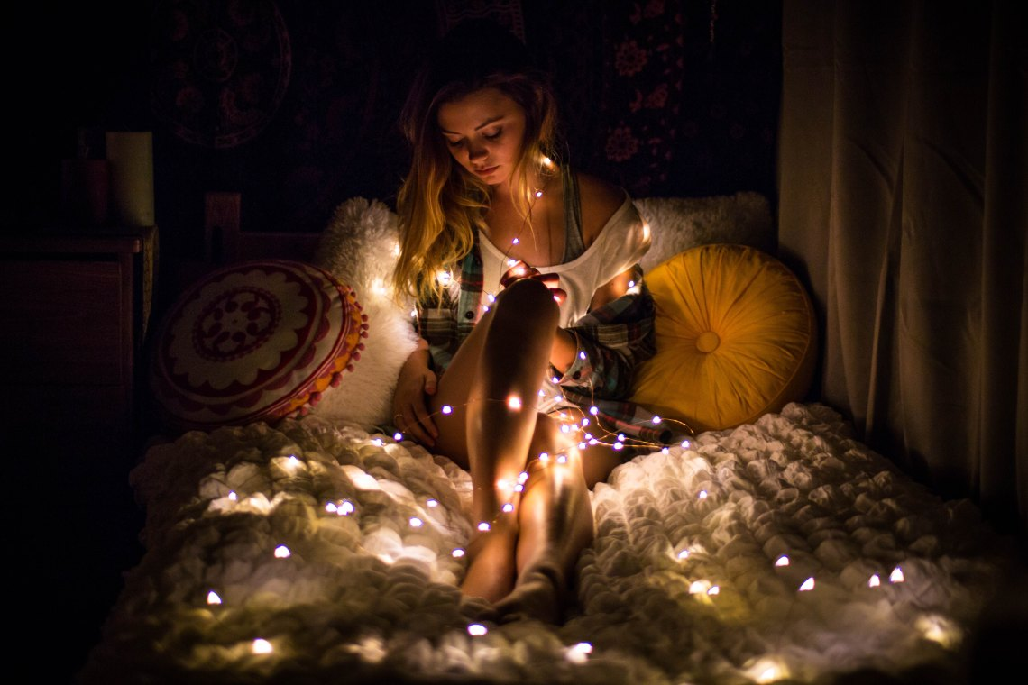 woman wrapped in christmas lights
