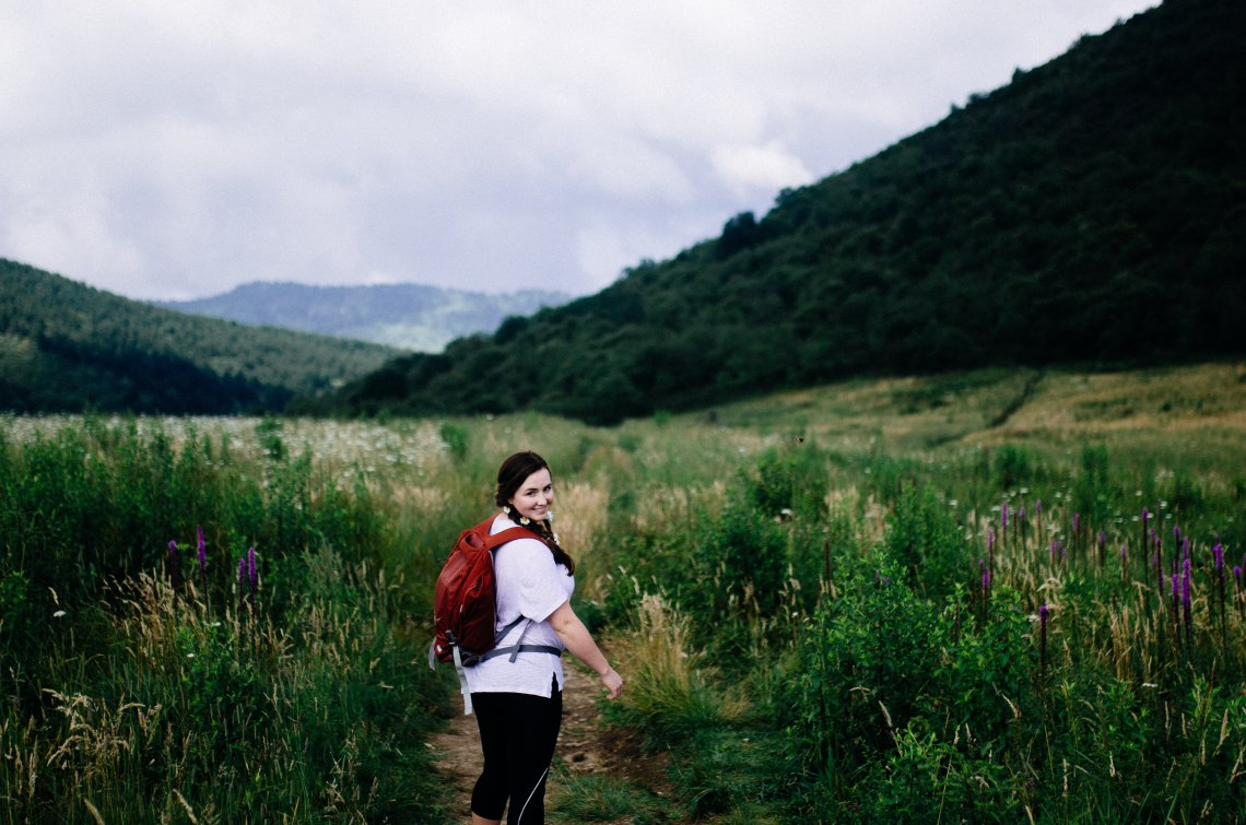 girl hiking in a pretty field