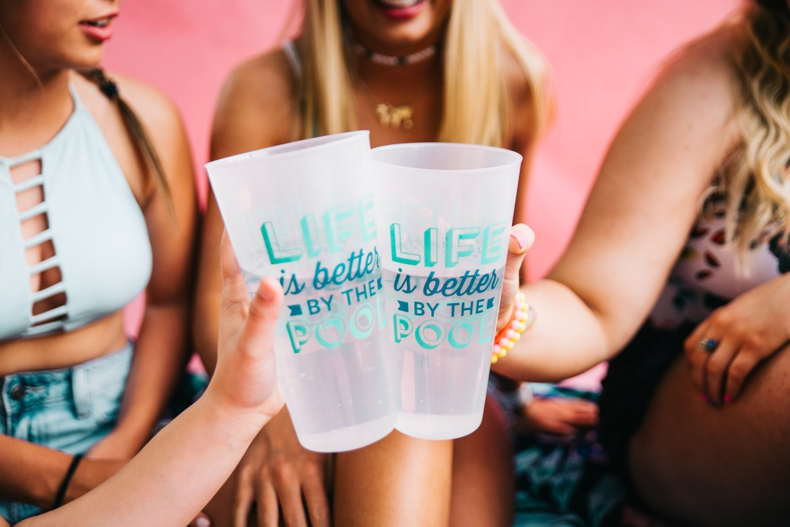 friends cheersing with plastic cups
