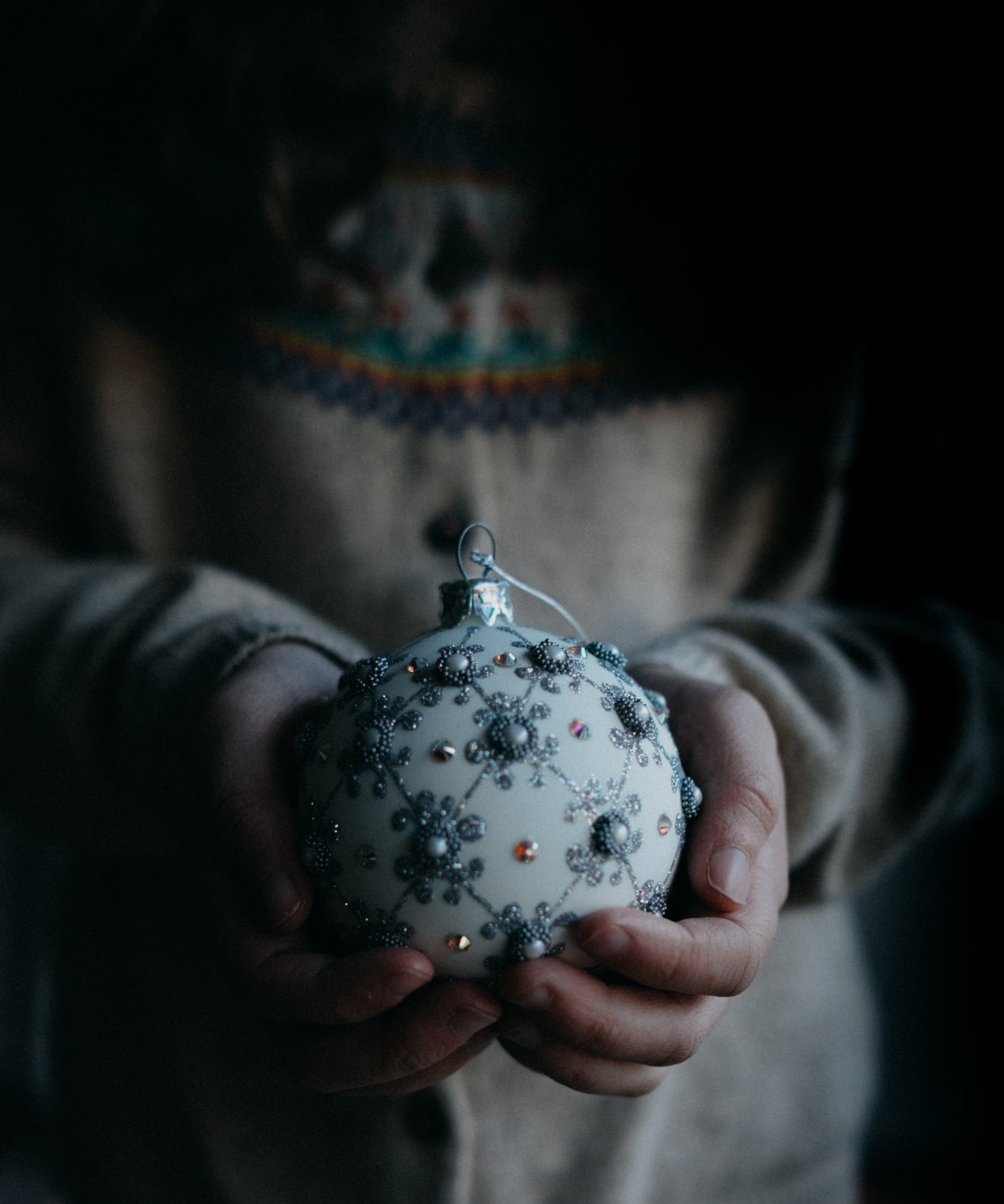 girl holding a dimly lit christmas ornament