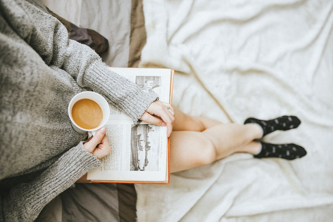 woman reading with coffee in bed