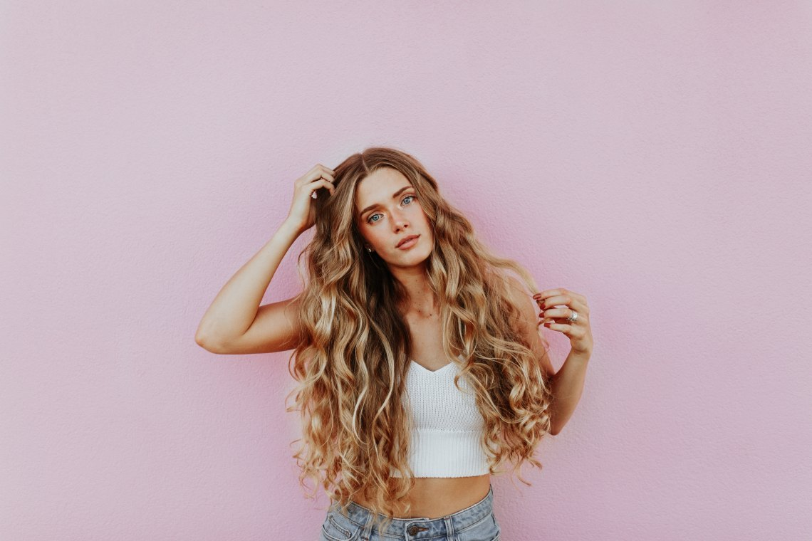 girl standing in front of a pink wall