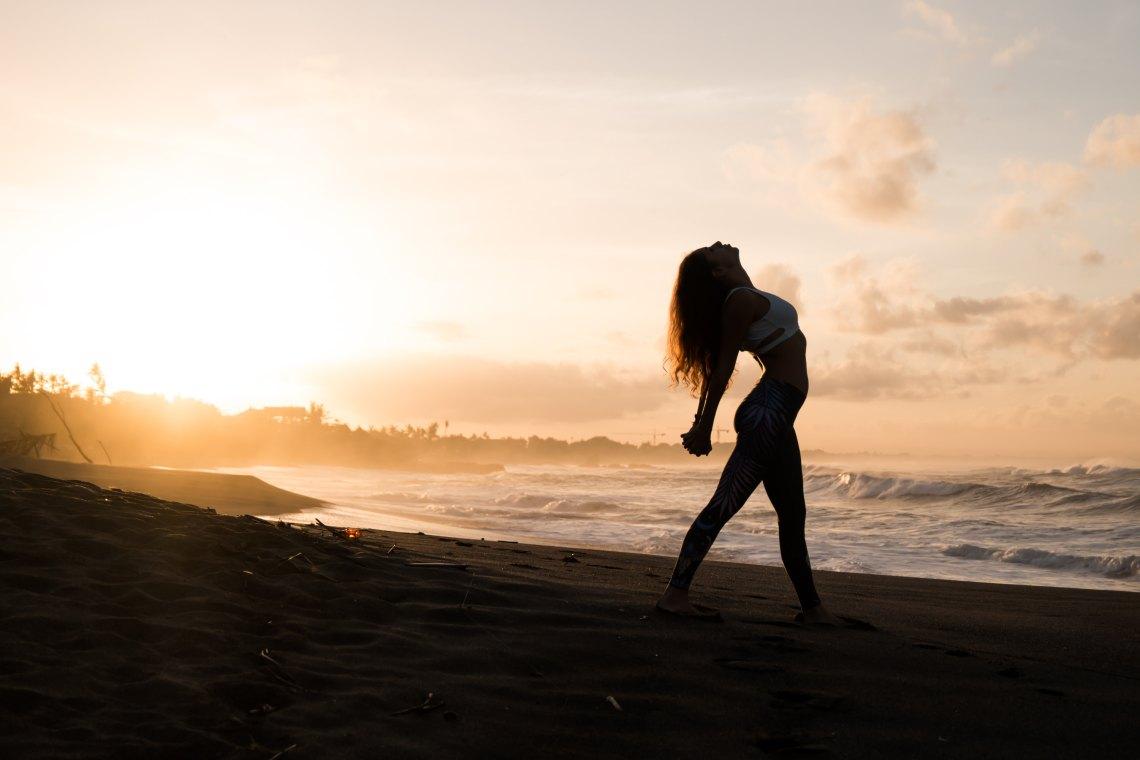 girl doing yoga by the ocean