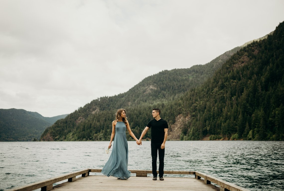 couple on a dock in front of a mountain