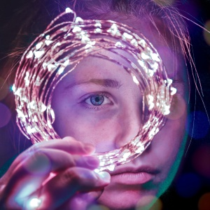 girl holding up a string of lights