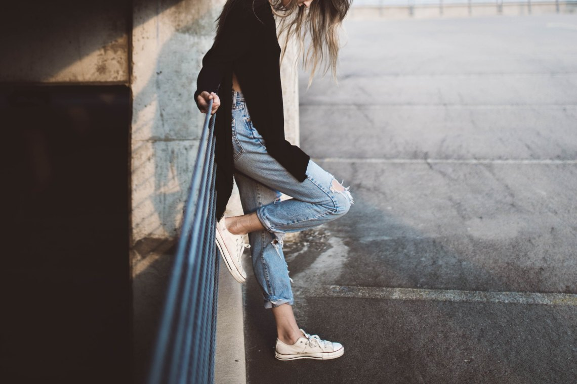 woman leaning against post with ripped jeans