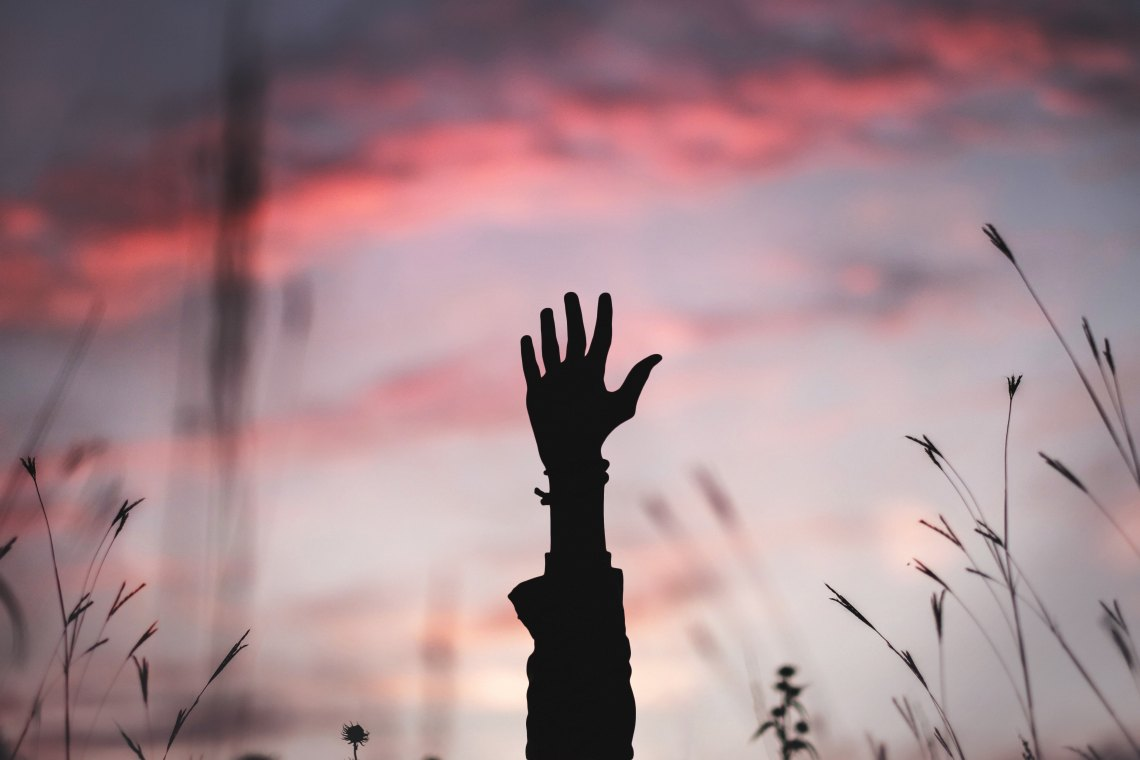 a hand reaching up over a sunrise