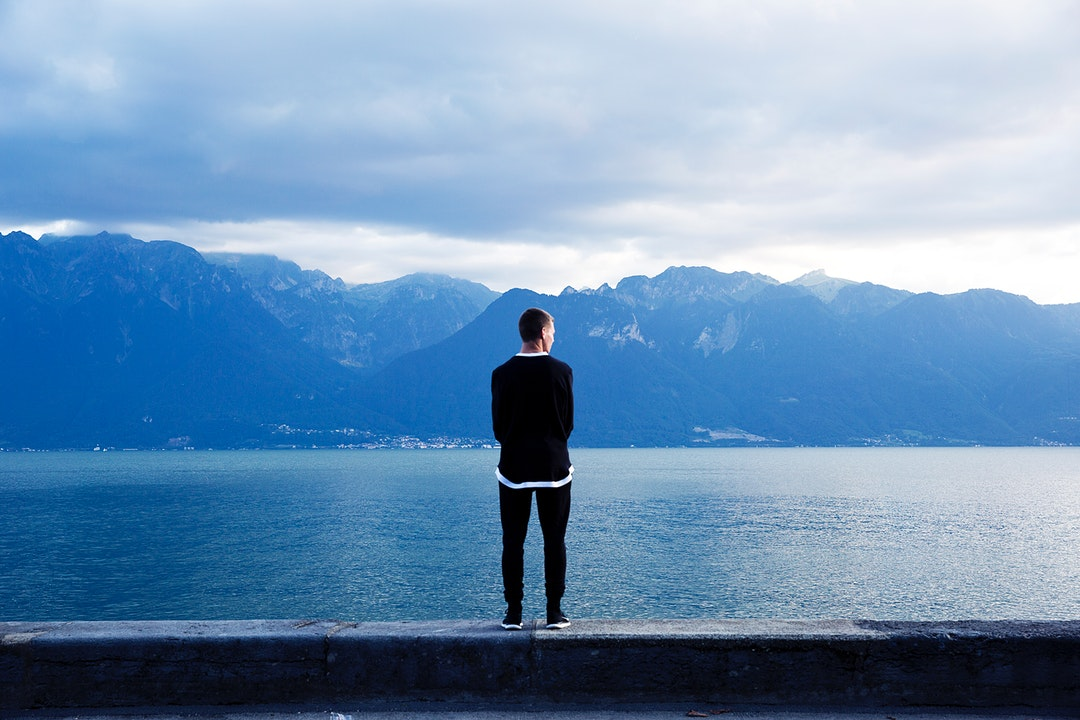 A man standing on a stone ledge and looking off into the mountain lake