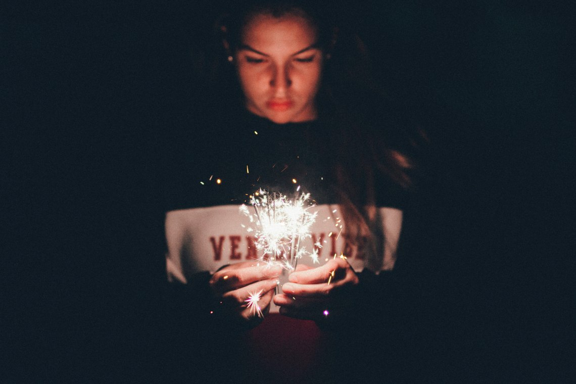girl in a sweater with a sparkler