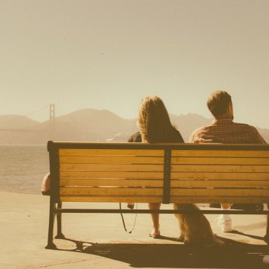 A man and a woman sit on a bench, looking out into the distance, probably about to break up