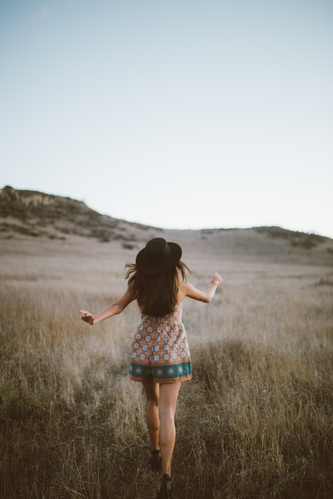 woman walking away in field