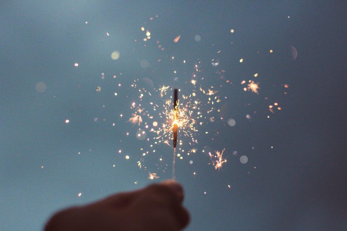 hands holding sparkler at dusk