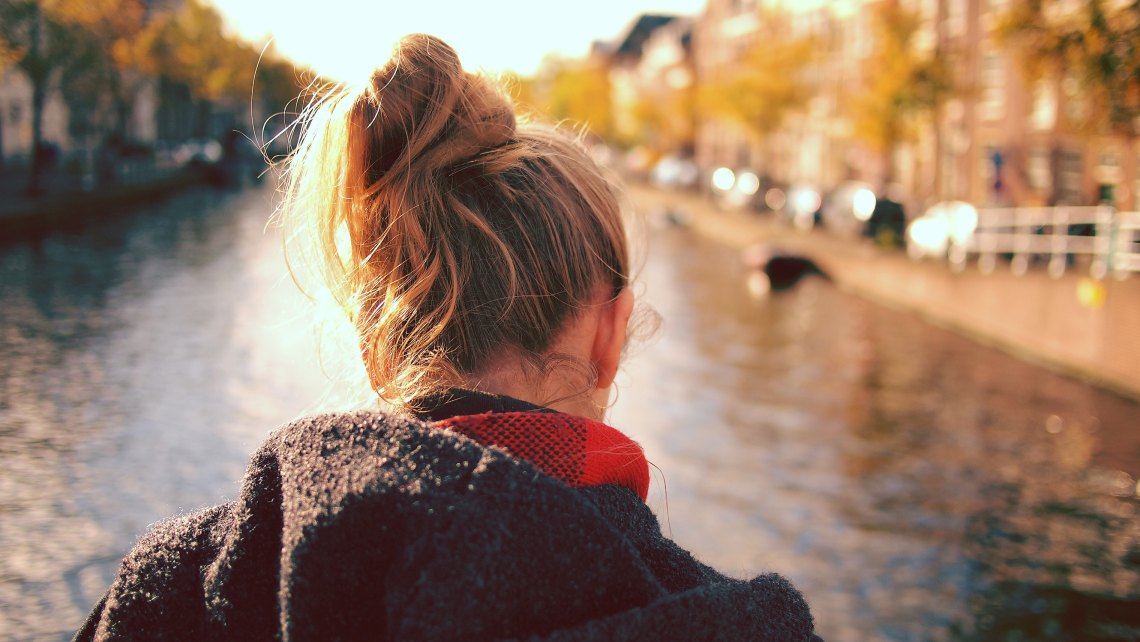 back of woman's head in front of a river