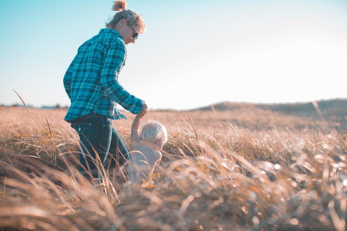 Mom and kiddo running through a wheat field