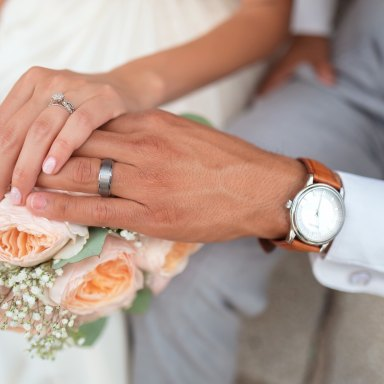 husband and wife hold hands, showing off their wedding rings