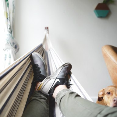 man in a hammock with a dog watching him