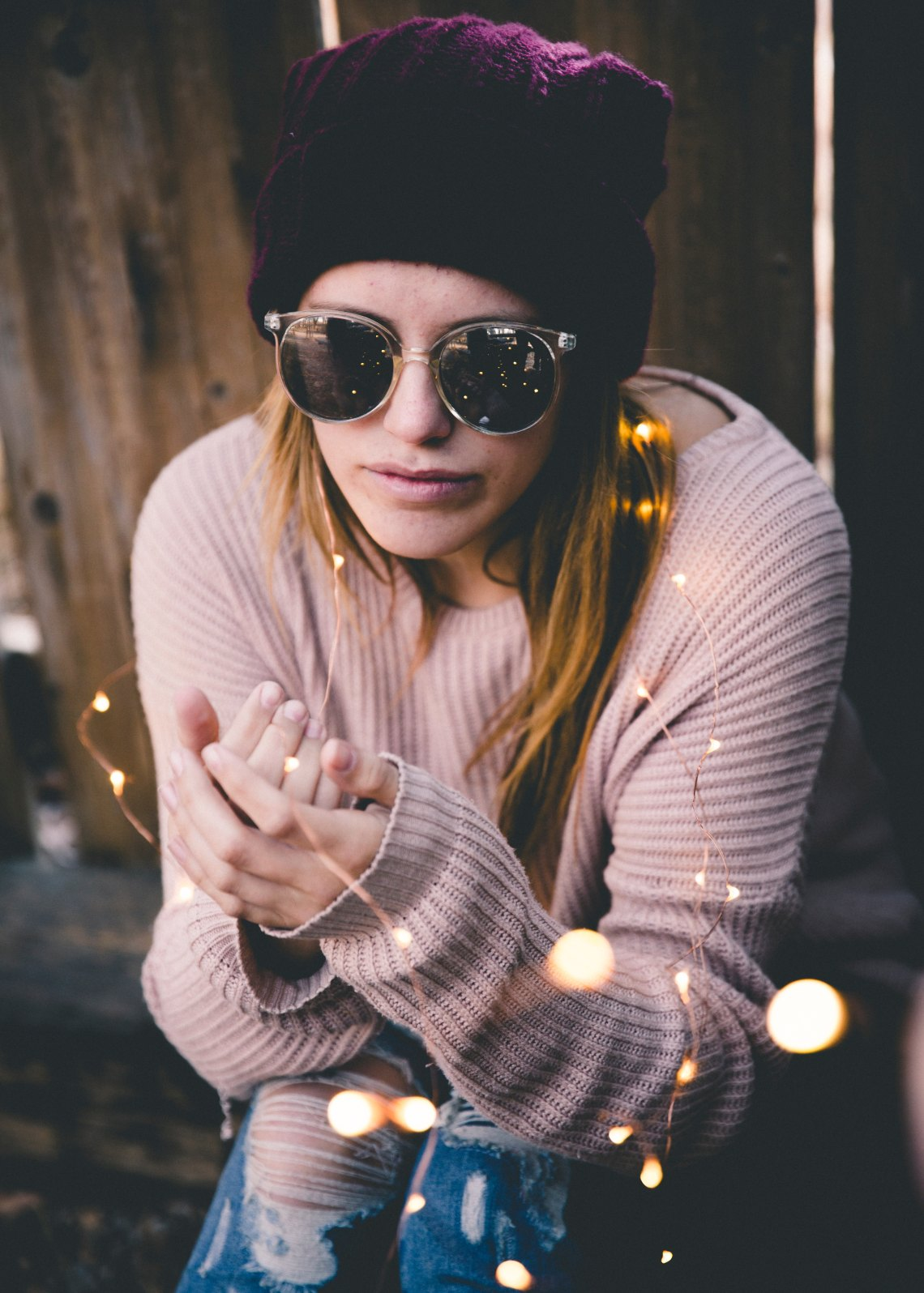 girl in a sweater with sunglasses and twinkle lights