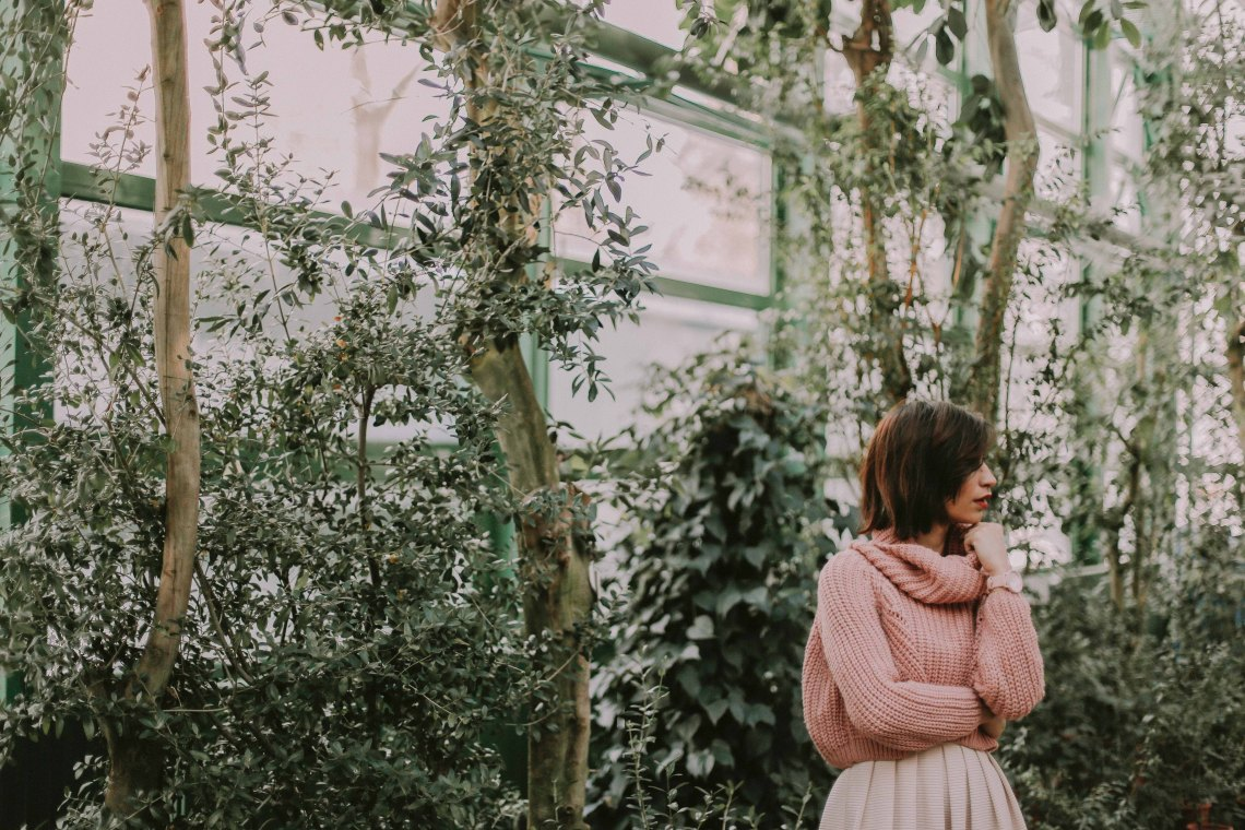 woman in a pink sweater in a greenhouse