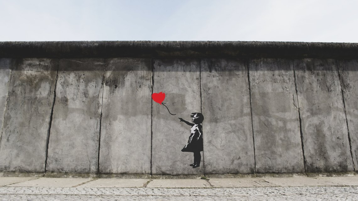 graffiti of a woman holding a heart balloon on the Berlin wall