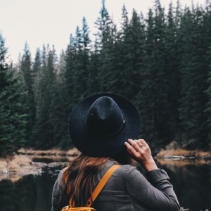 woman wandering through the forest in her hat