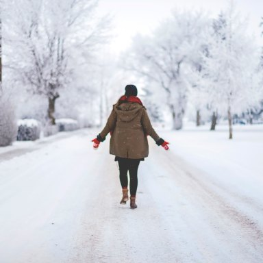 woman walks along a path of snow