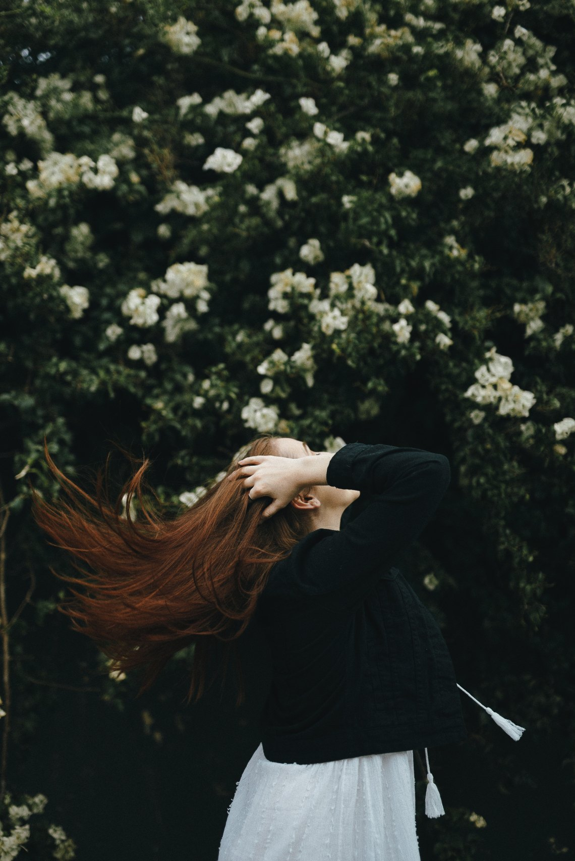 woman flipping hair by some flowers