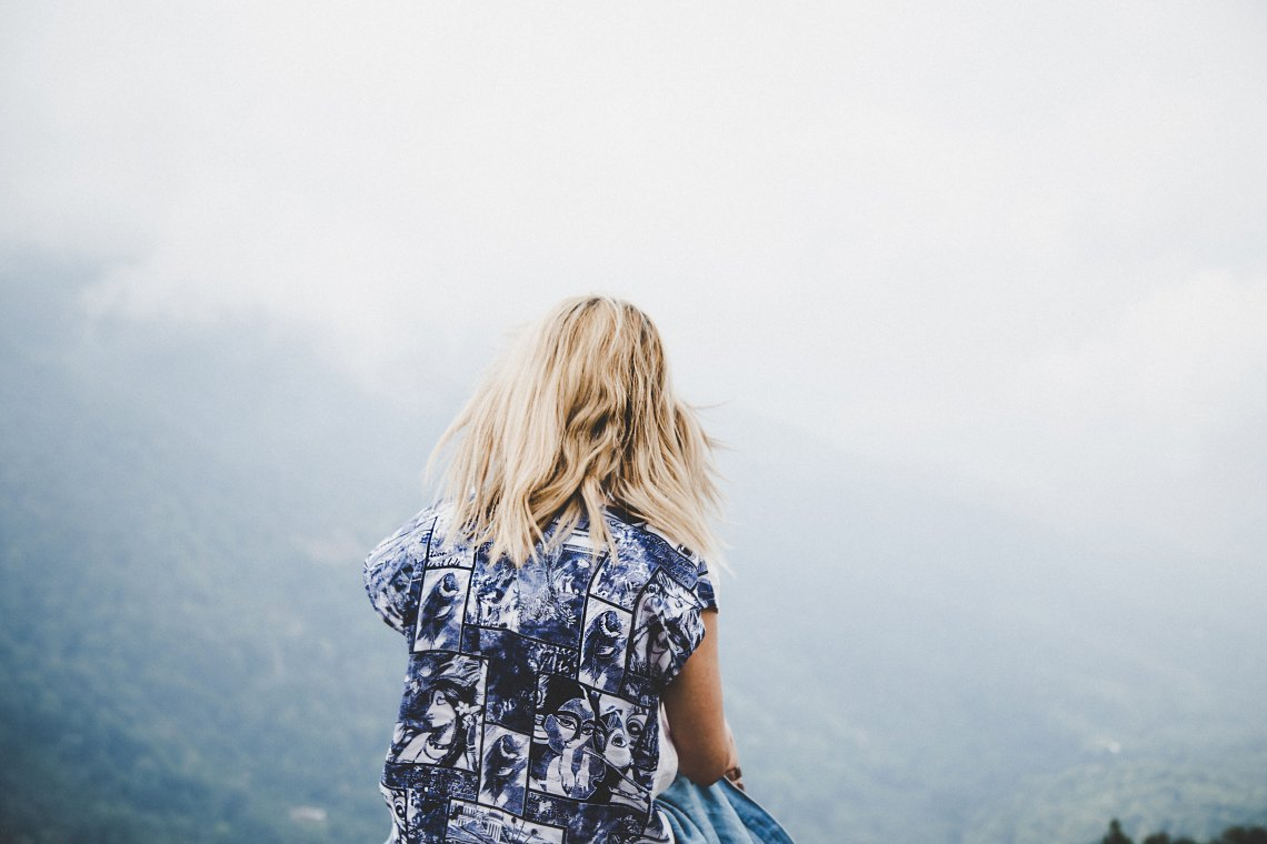 girl patterned blue shirt with her back turned