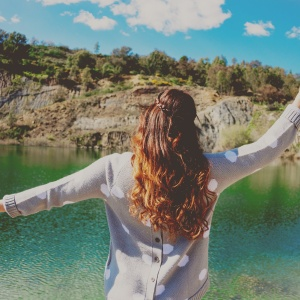 woman standing in front of lake carefree