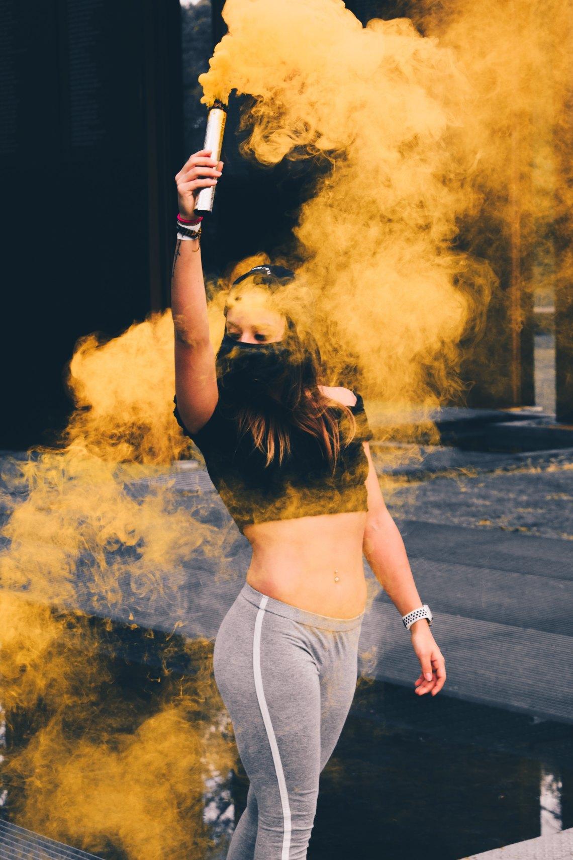 girl wandering around with yellow smoke