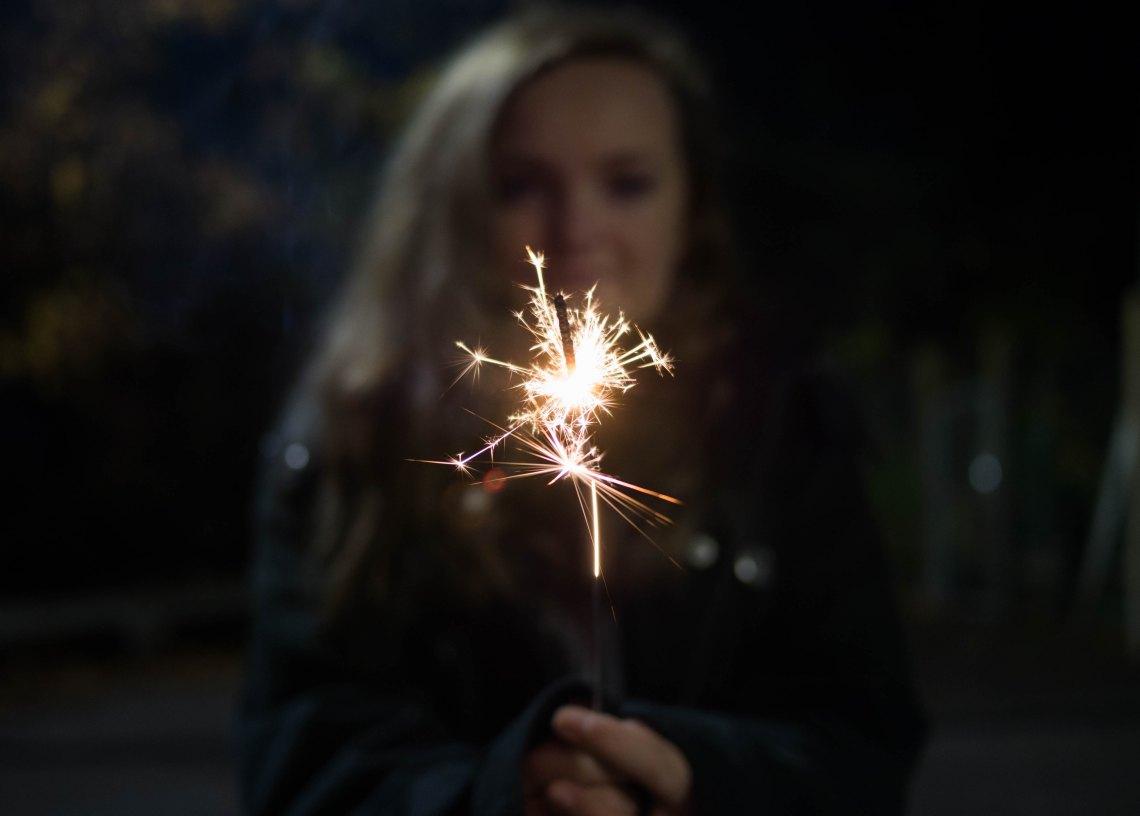 girl holding a sparkler backlit