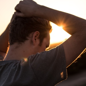 man standing in front of sunset