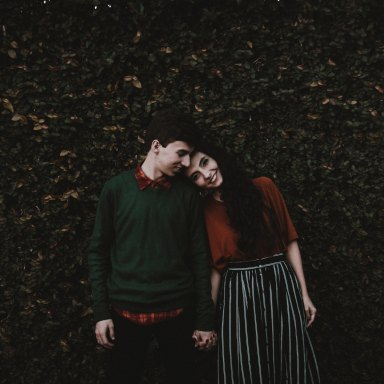 Couple holding hands in greenery