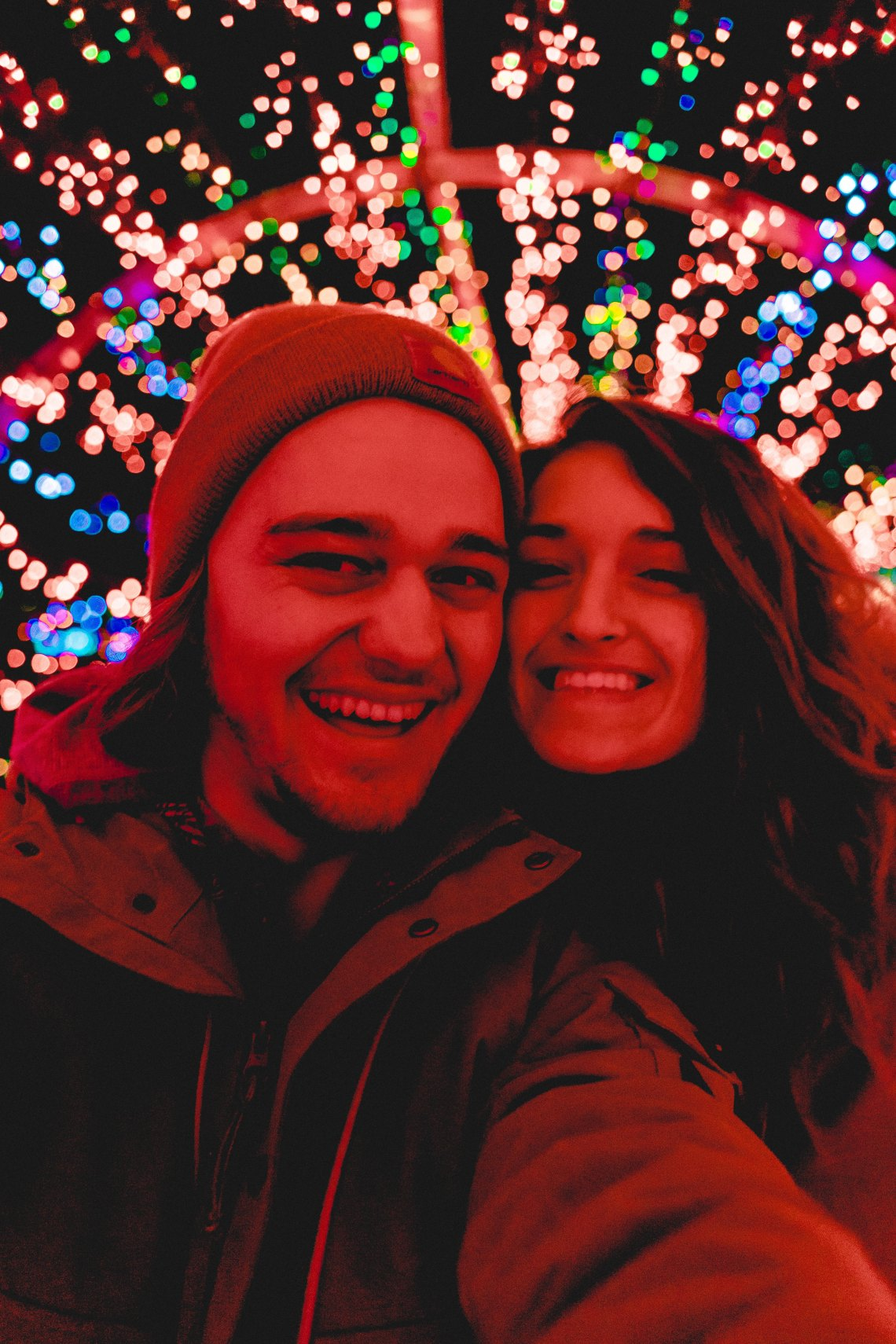 couple in front of chrismtas lights