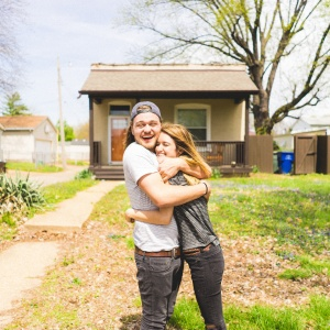 couple hugging in front of their home
