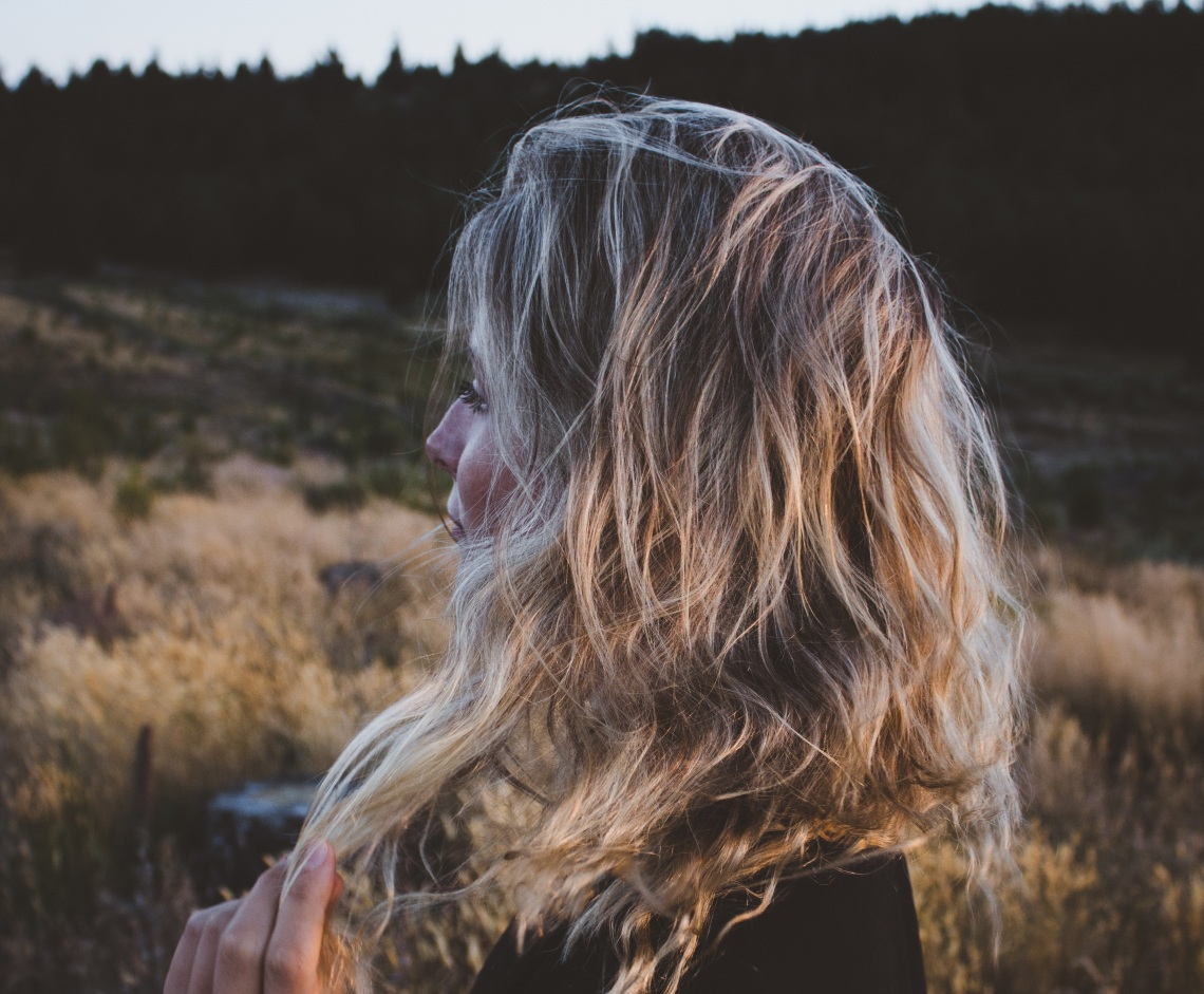 girl looking out at field, blonde, calm expression, brokenness, romanticizing brokenness, fear of feeling good