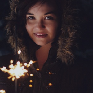 woman holding sparkler in winter