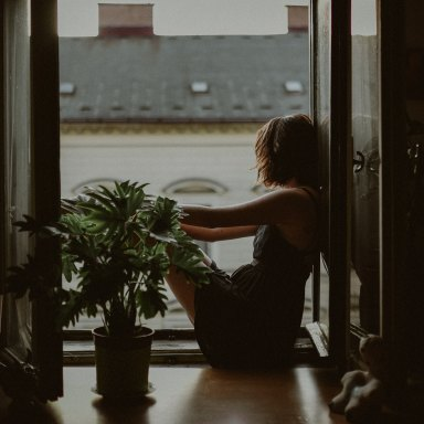 woman sitting looking outside of window