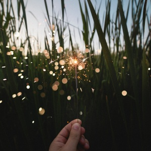 a hand holding up a sparkler in front of grass