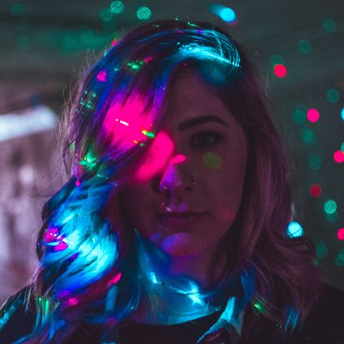 woman with christmas lights behind her and on her face