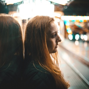 girl leaning against a mirror next to a street