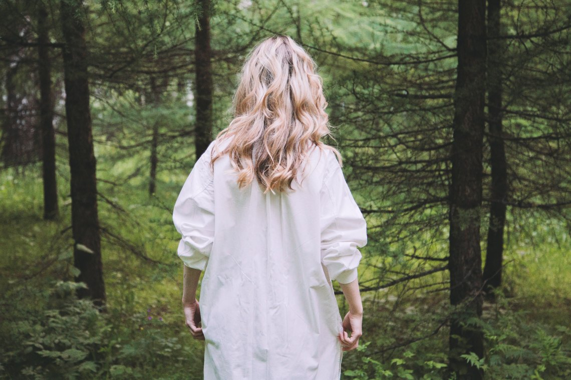 blonde girl walking away in a forest