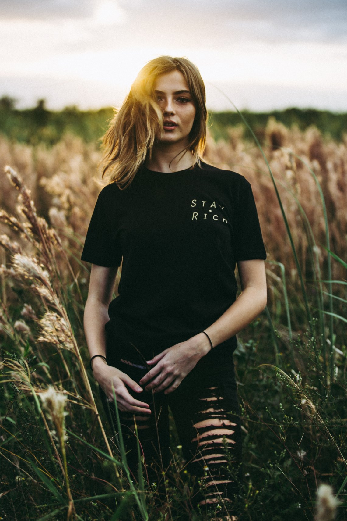 girl standing in a field in a stay rich shirt