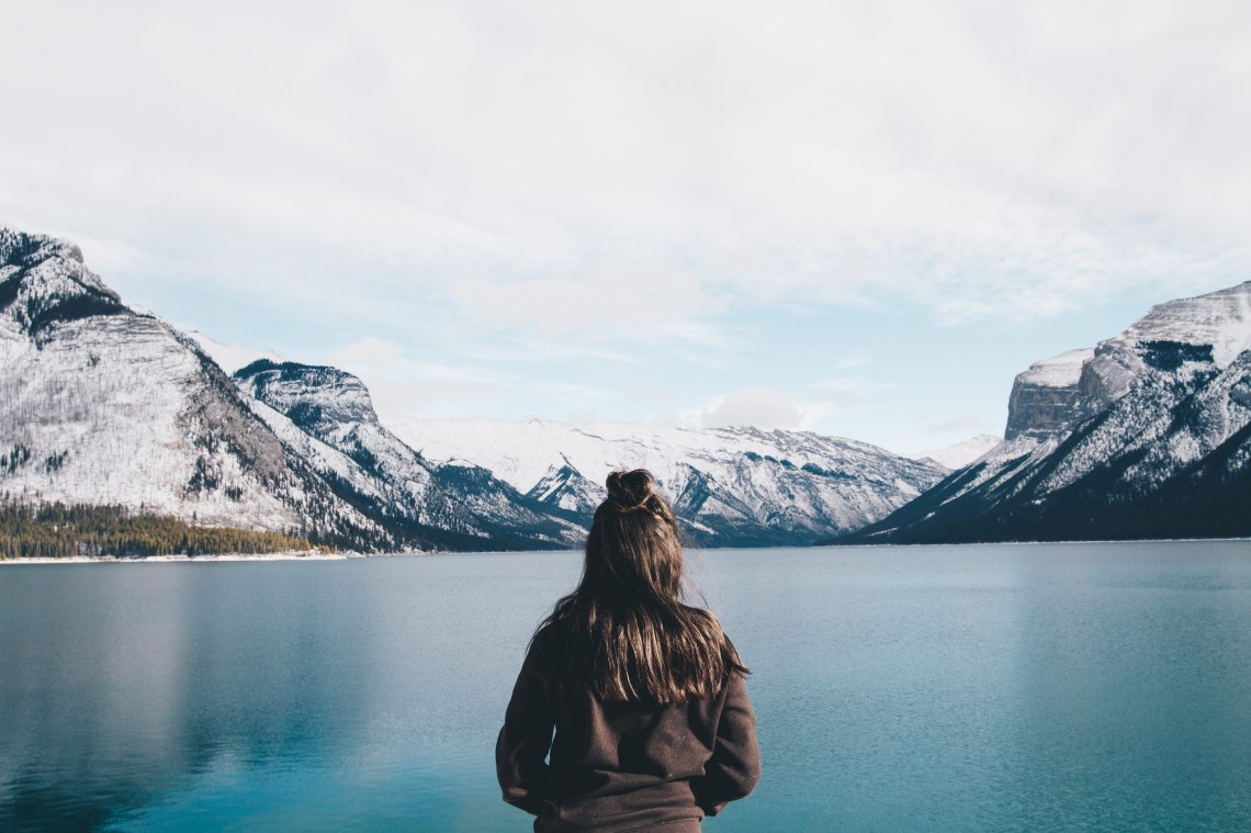 girl standing in front of a lake