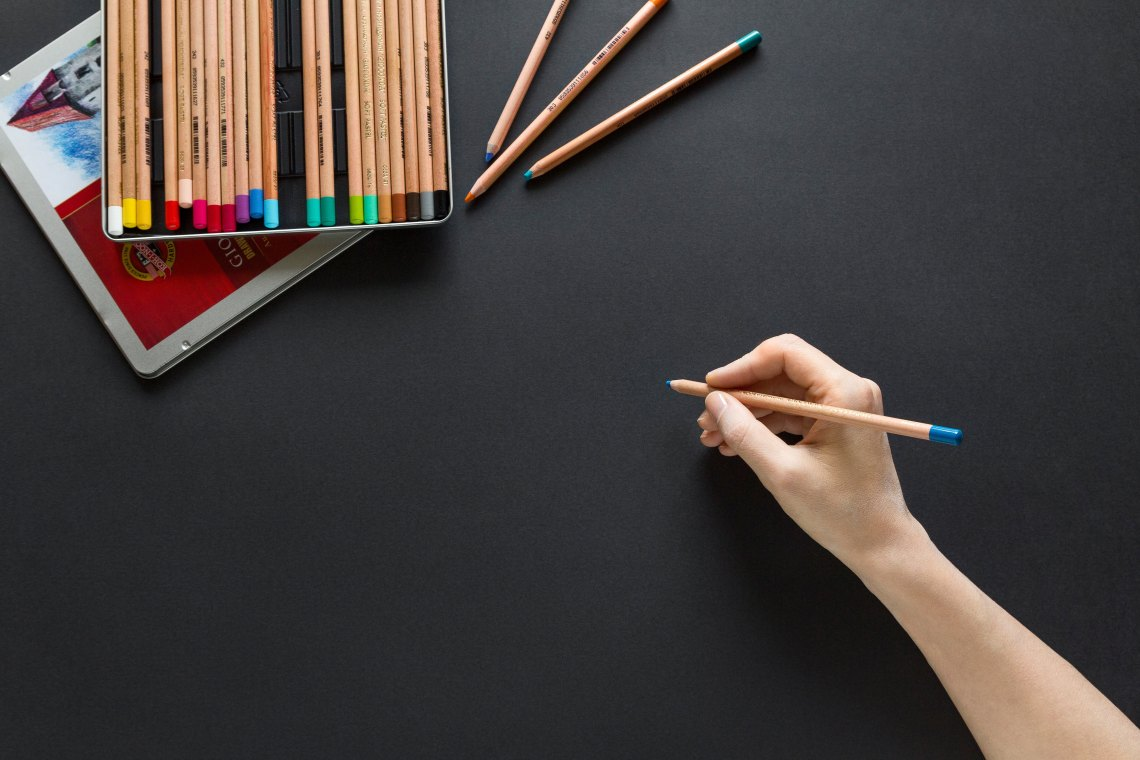 Person drawing with a colored pencil