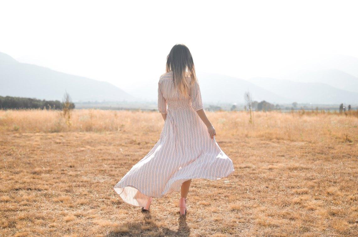 girl twisting her skirt in an open field